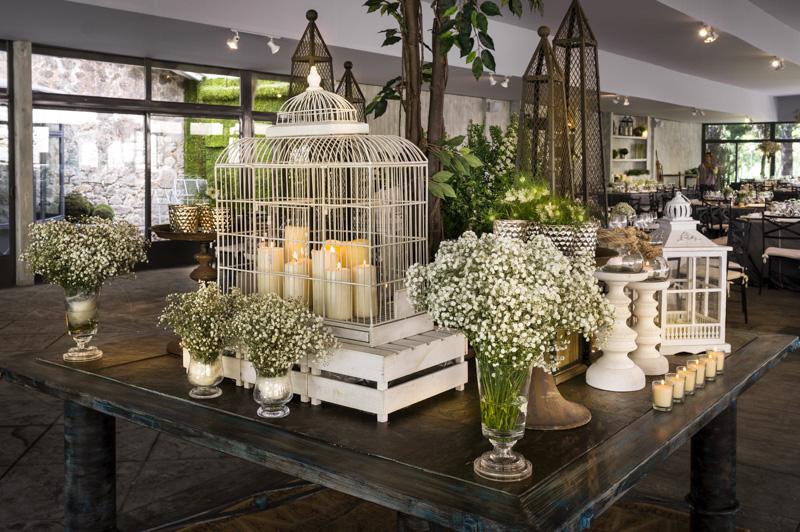 Boda El Campillo. Bodegón: jaula con velas, obeliscos de forja, candiles, fotóforos,  jarrones de cristal con paniculata,  alstroemerias y tulipanes.